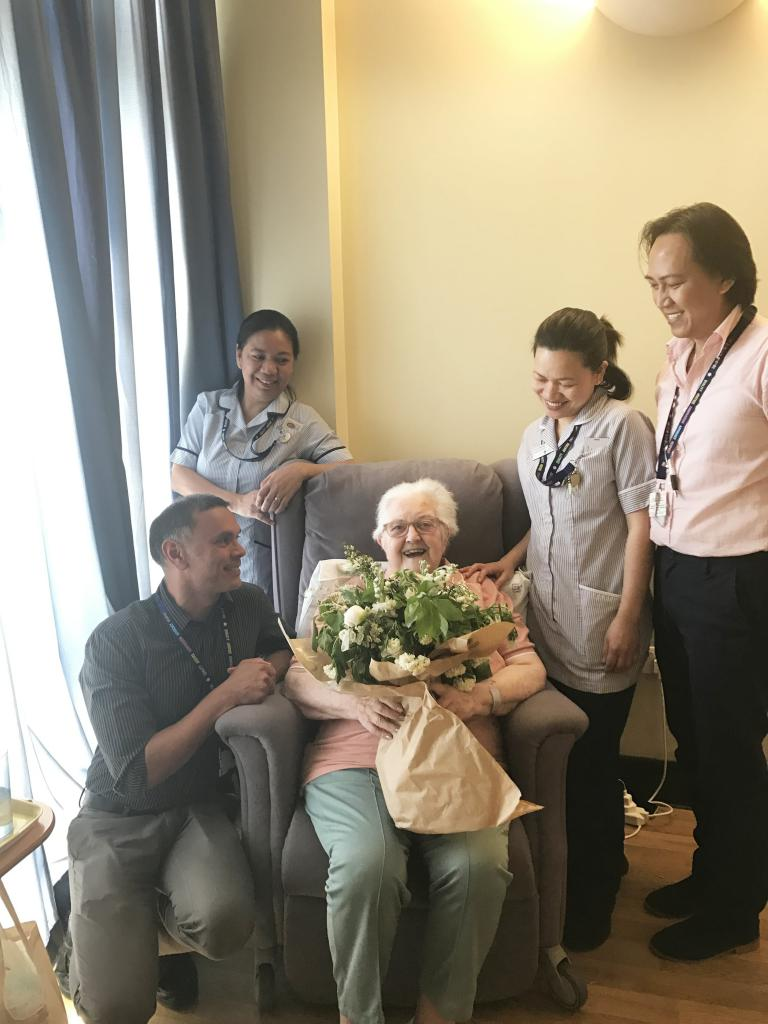 Resident Pauline Clayton and staff at St Joseph's display the royal bouquet
